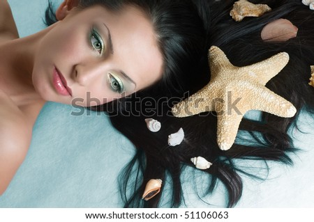 Beauty brunette with sea shells in hair