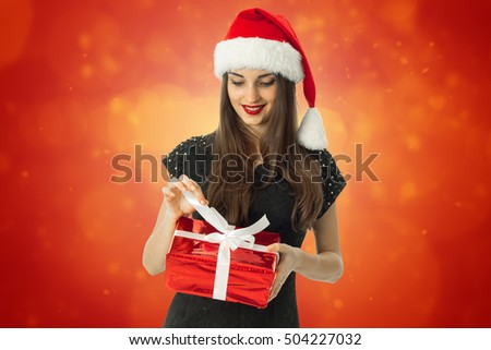 beauty brunette woman in santa hat smiling with red gift in hands on red background