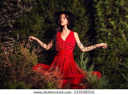 Beauty brunette women in red dress & hat pose at night park. - stock photo