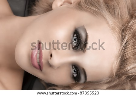 beauty close up of a gorgeous blonde girl with sophisticated smokey eyes make up