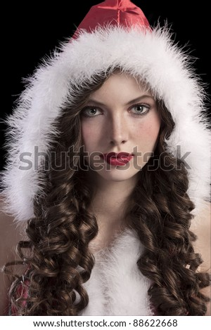 beauty close up of a gorgeous sweet teen girl with long brunette curles and wearing a red santa hood with white fur - stock photo