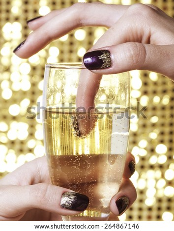 beauty close up photo fingers with creative manicure holding glass of champagne on gold background, celebration idea - stock photo