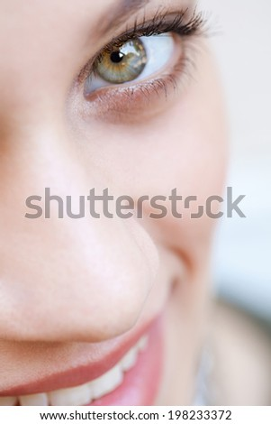 Beauty close up portrait section detail of an attractive young woman looking up with clear green eyes and wearing cosmetics, smiling. Healthy skin, beauty and sight care, well being. - stock photo
