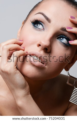 Beauty closeup of an attractive brunette posing on grey background - stock photo