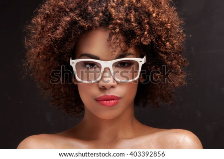 Beauty closeup portrait of young  african american girl with afro. Ideal skin. Woman in fashionable eyeglasses. - stock photo