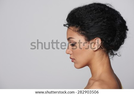Beauty closeup profile portrait of beautiful mixed race caucasian - african american woman looking forward isolated on gray background - stock photo