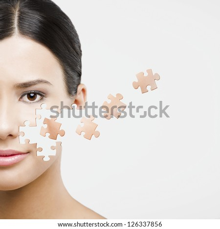 Beauty concept of a beautiful Asian woman with puzzle pieces in the face - stock photo