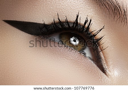 Beauty, cosmetics & make-up. Beautiful female eye with black liner makeup. Fashion catwalk visage. Sexy retro pin-up or rock diva's style. - stock photo