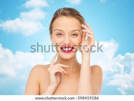 beauty, cosmetics, people and health concept - smiling young woman with pink lipstick on lips touching her face over blue sky and clouds background - stock photo