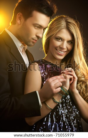 Beauty couple holding engagement ring - stock photo