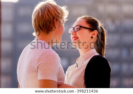 Beauty Couple relaxing on the balcony together. Teenage girlfriend and boyfriend having fun outdoors, kissing and hugging, first love concept. Teenagers Boy and Girl in love together - stock photo