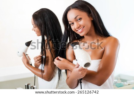 Beauty drying hair. Beautiful young African woman drying hair and smiling while standing in bathroom and against a mirror  - stock photo