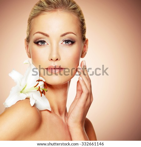 Beauty face of the young beautiful girl with flower. Female touching skin.  - stock photo