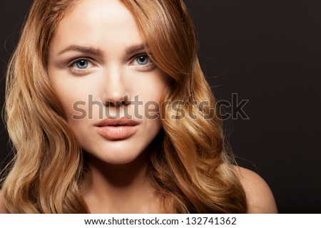 Beauty face of woman with fresh skin and long hair on dark background - stock photo