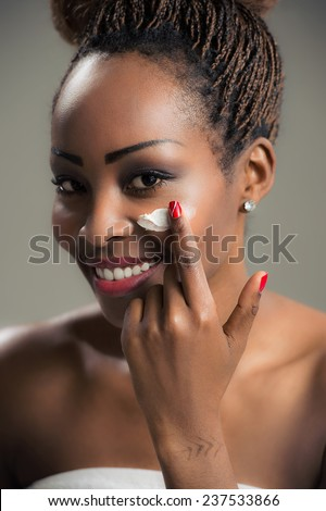 Beauty face of young african american woman with cosmetic cream on a cheek. Skin care concept. Closeup portrait. - stock photo
