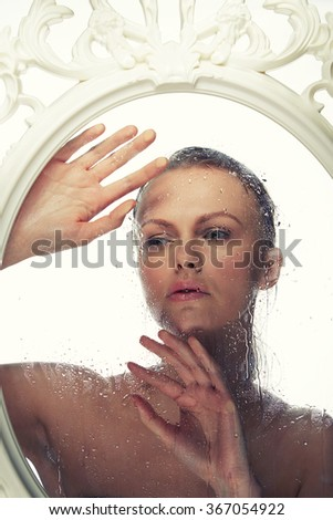 Beauty face of young caucasian woman near a mirror in baroque frame with water drops. Toned - stock photo