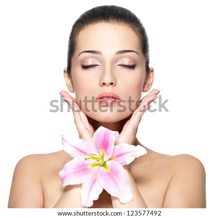 Beauty face of young woman with flower. Beauty treatment concept. Portrait of young woman with closed eyes - stock photo