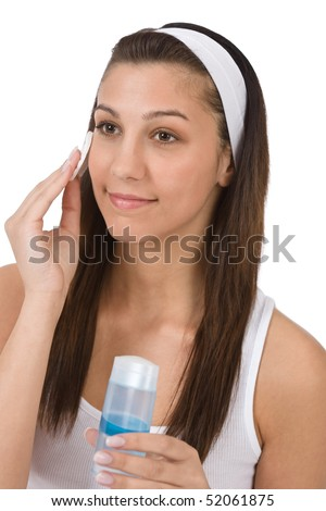 Beauty facial care - Teenager woman cleaning acne skin with cotton pad on white background - stock photo