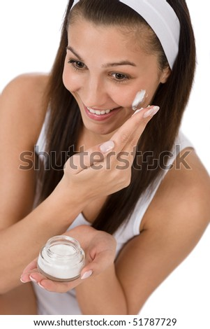 Beauty facial care - Young woman apply moisturizer on white background - stock photo