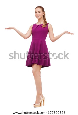 beauty, fashion, advertisement and happy people concept - young woman in purple dress and high heels holding something on palm of her hands - stock photo