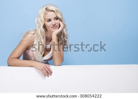 beauty, fashion and young woman in pink dress on blue background holding empty white board - stock photo