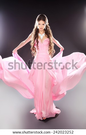 Beauty fashion girl model posing in blowing transparent chiffon dress with voluminous skirt over dark lights background - stock photo