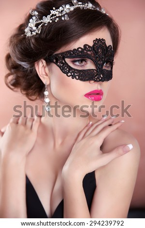 Beauty fashion girl model with mask. Makeup. Hairstyle. Jewelry. Sensual woman wearing venetian masquerade carnival mask - stock photo