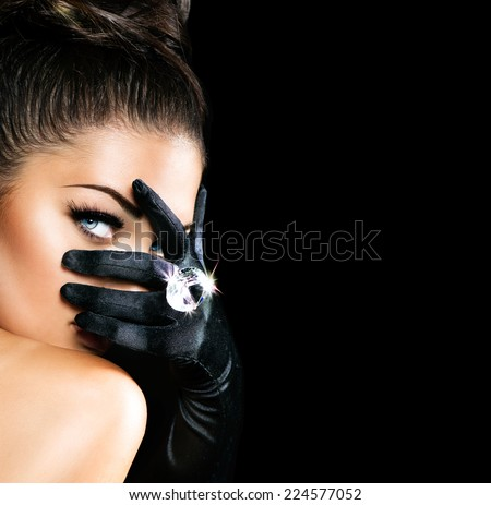 Beauty Fashion Glamorous Model Girl Portrait. Vintage Style Mysterious Woman Wearing black Glamour Gloves. Jewellery. Jewelry. Holiday Hairstyle and Make-up. Diamond Ring. Retro Lady with Blue Eyes  - stock photo