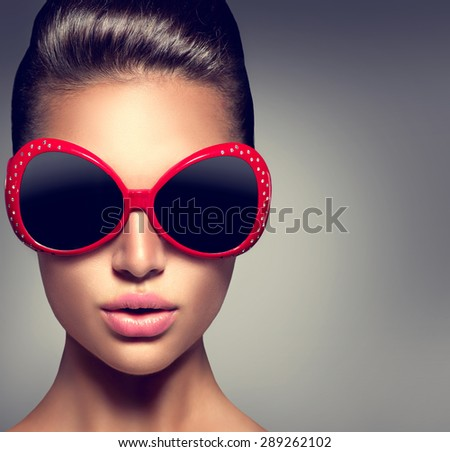 Beauty Fashion model brunette girl wearing stylish sunglasses. Beautiful Lady face. Sexy woman portrait over dark background - stock photo