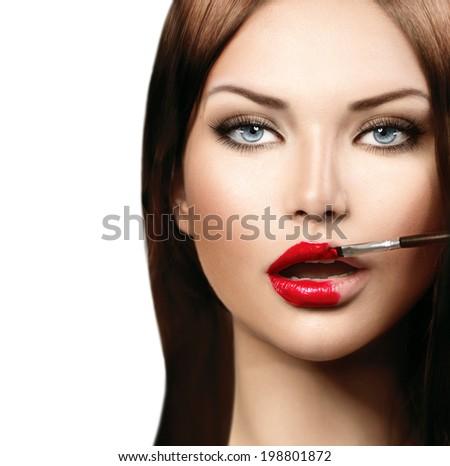 Beauty fashion model girl applying red lipgloss. Lipstick. Professional Make-up. Makeup. Lipgloss. Lipstick Brush. Sexy and Glossy Lips  - stock photo