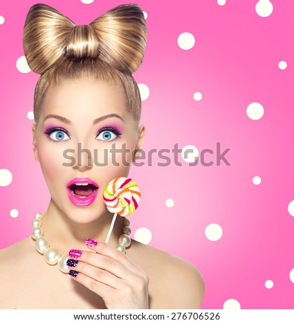 Beauty fashion model girl Eating colourful lollipop. Surprised Young funny woman with bow hairstyle, pink nail art and makeup over pink polka dots background - stock photo