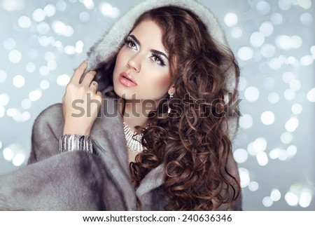 Beauty Fashion Model Girl in Mink Fur Coat and furry hood. Beautiful Luxury Winter Woman isolated on bokeh Christmas lights background. - stock photo