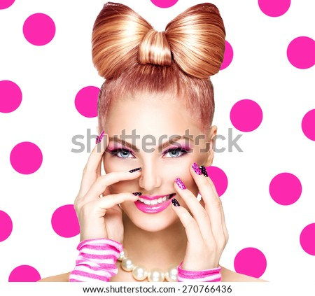 Beauty fashion model girl with funny bow hairstyle, pink nail art and makeup over polka dots background. Colourful Studio Shot of Funny Woman. Vivid Colors. Emotion - stock photo