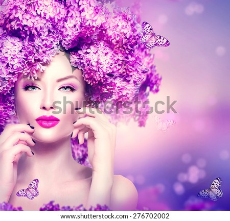 Beauty fashion model Girl with Lilac Flowers Hair Style. Beautiful Model woman on Blooming purple flowers background with butterfly. Nature Hairstyle. Holiday Makeup and manicure. Make up Vogue Style  - stock photo