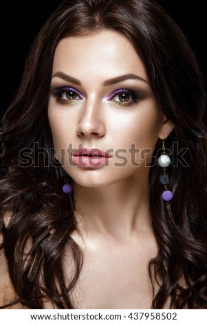 Beauty Fashion Model Girl with long hair. Brunette Model Portrait. Sexy Woman Makeup and Accessories. Isolated on black. Purple Earrings