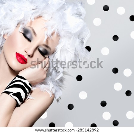 Beauty Fashion Model Girl with White Feathers Hair style and bright make up. Beautiful woman with feathers on her head. Hairstyle. Holiday Creative Makeup and manicure. Polka dots background - stock photo