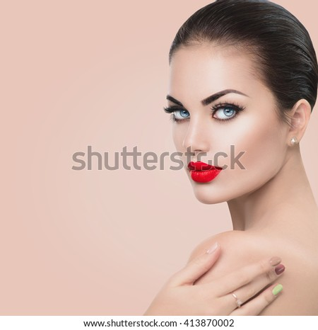 Beauty Fashion Model Woman face. Portrait with Red sexy lips and blue eyes, perfect make up. Beautiful Brunette Woman with Luxury Makeup touching her soft skin shoulder. Skin care. Beige background - stock photo