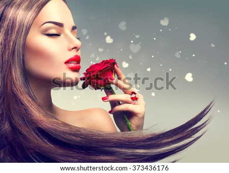 Beauty Fashion Model Woman with red rose flower. Red Lips and Nails. Valentine's Day Beautiful Fashion sexy Girl with flying long hair. Beautiful Sexy Brunette with Luxury Makeup and Manicure - stock photo