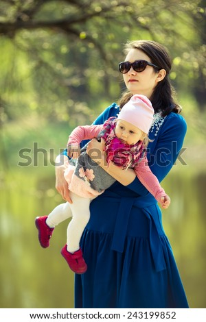 Beauty fashion Mom holding daughter in arms. Adorable toddler girl. Park. Summer. Magic beauty natural light - stock photo