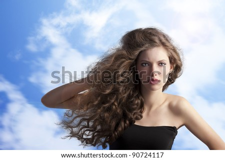 beauty fashion portrait of a very young cute brunette with long curly hair with hairstyle flying in the wind on sky background - stock photo