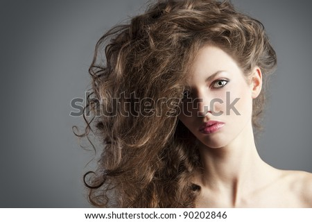 beauty fashion portrait of beautiful young brunette with curly hair flying and creative hairstyle, she is in foreground, looks in to the lens and has tuft on the right.