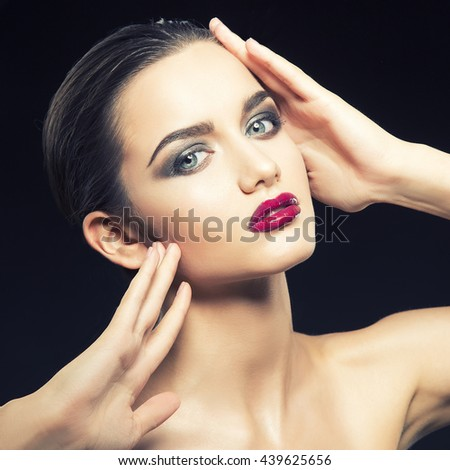 Beauty fashion portrait of caucasian brunette woman wet wet red lipstick and arms touching face. Isolated on black background. Toned - stock photo