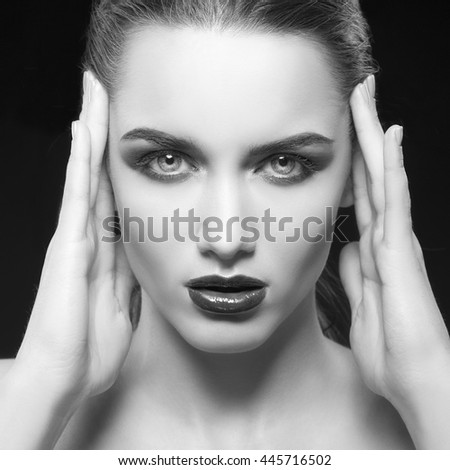 Beauty fashion portrait of caucasian brunette woman wet wet red lipstick and arms touching face. Isolated on black background. Black and white
