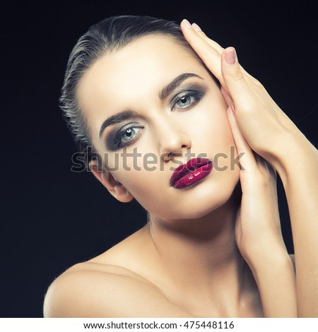 Beauty fashion portrait of caucasian brunette woman wet wet red lipstick and arms touching face. Isolated on black background. Toned