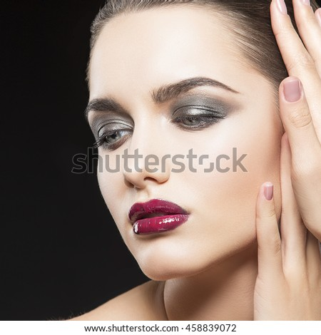 Beauty fashion portrait of caucasian brunette woman with wet red lipstick and arms touching face. Isolated on black background.
