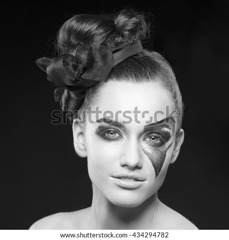 Beauty fashion portrait of caucasian young brunette girl with party comics make-up with sparkles looking at camera. Studio portrait. Black and white