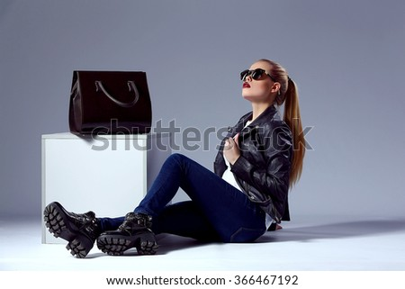 Beauty fashion portrait of Vogue style amazing young blond woman with bright make-up, dark sunglasses with black bag near cube in studio - stock photo