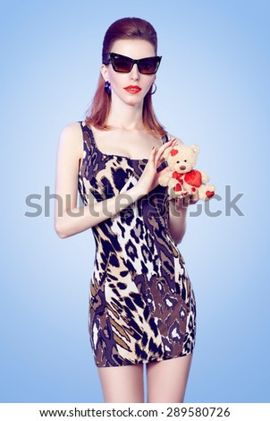 Beauty  fashion sexy slim model redhead woman in stylish mini dress holds loving teddy bear with red heart on blue. Sensual lady in sunglasses. Provocative young people, playful flirty mood. Copyspace - stock photo