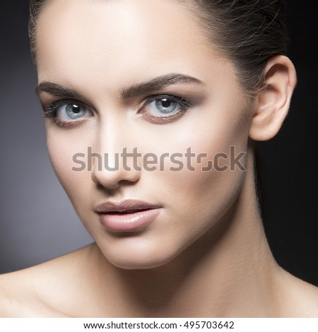 Beauty fashion vogue style face of caucasian brunette with elegant make-up, blue eyes, natural lips touching perfect skin. Close-up studio portrait isolated. Black background with grey spot.