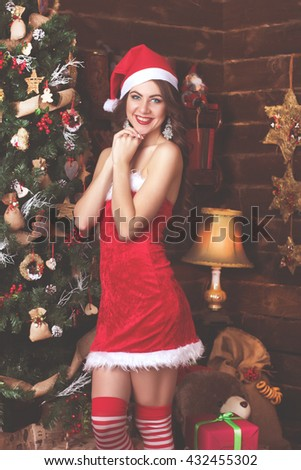 Beauty fashion woman in sexy dress.  Woman near a Christmas tree. Picture toned in sepia tone - stock photo